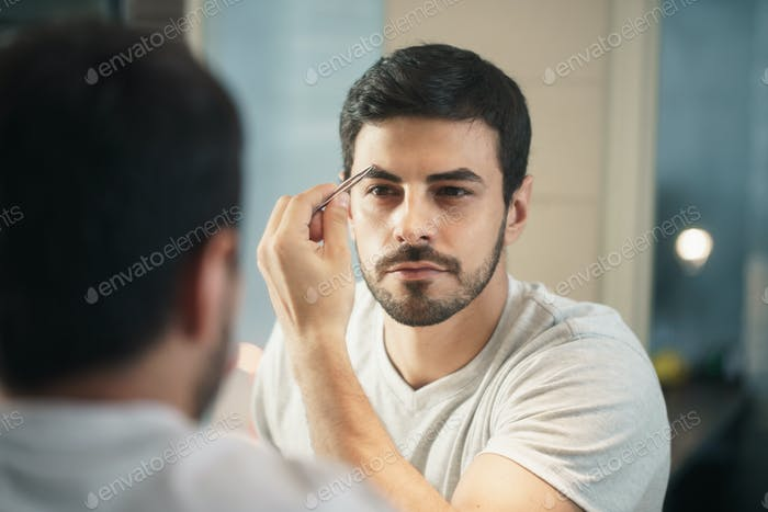Thumbnail for Latino Man Trimming Eyebrow For Body Care In Bathroom