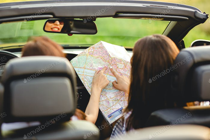 Two dark-haired women are sitting a black cabriolet and exploring the map