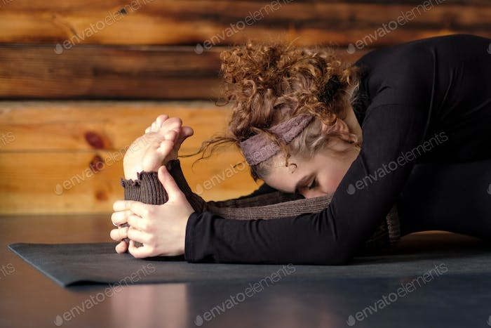 Woman practicing yoga stretching in Seated forward bend, paschimottanasana