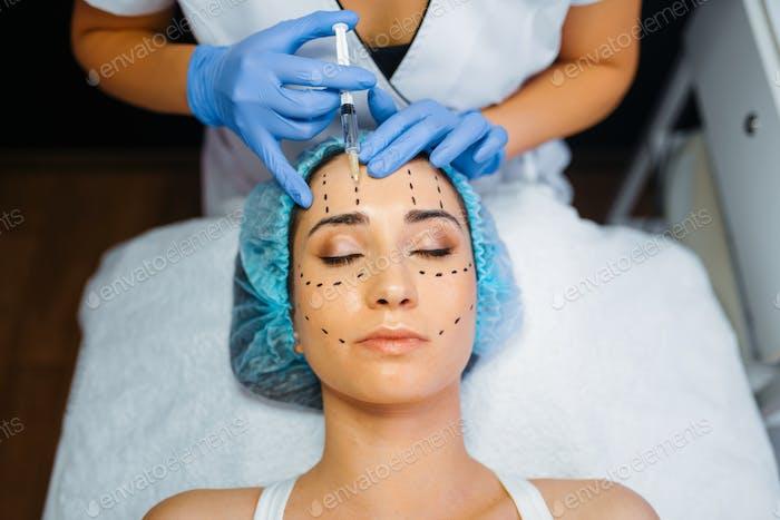 Kosmetikerin macht Botox-Injektion in gepunkteten Linien