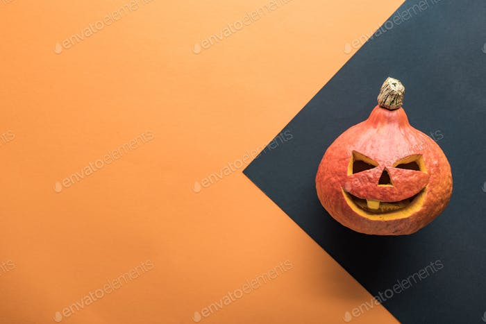 Top View of Carved Halloween Pumpkin on Orange And Black Background