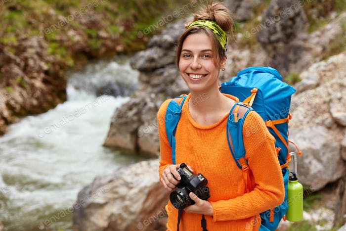 Positive young traveler poses with camera and backpack against canyon, enjoys nature and landscape,