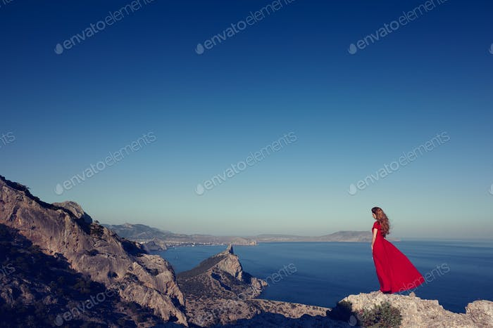 Young beautiful woman in red dress looking to mountains sea