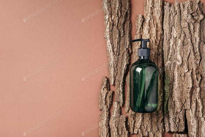 Green glass bottle of shampoo, soap, conditioner on beige background with natural bark, wood. Top