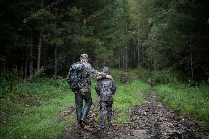 Cazadores con equipo de caza que se alejan a través del campo rural hacia el bosque al atardecer durante