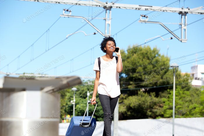 African american female walking by station with suitcase and mobile phone