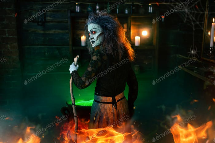 Scary witch cooking green brew and reads the spell
