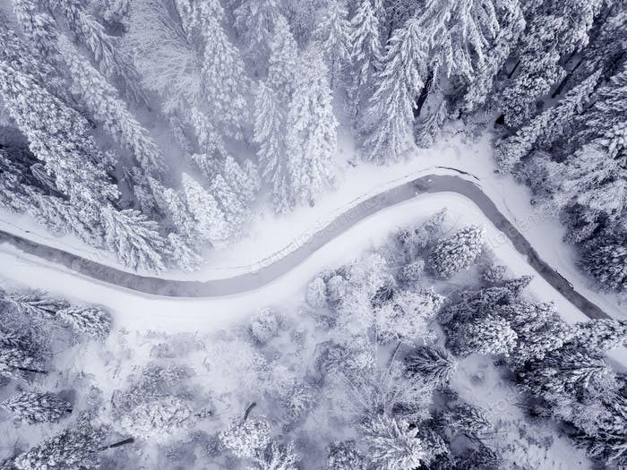 Straight down view of stream meandering through frozen, snow cov
