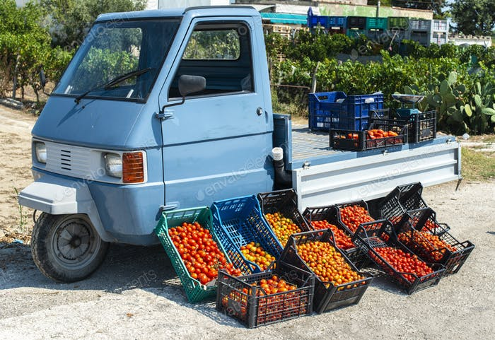 Small italian apo truck with tomatoes. Farmer sale tomatoes on t