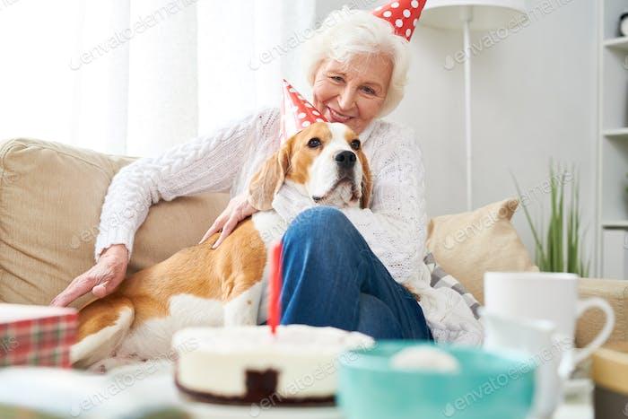 Lächelnde Senior Woman Feiern Geburtstag mit Hund