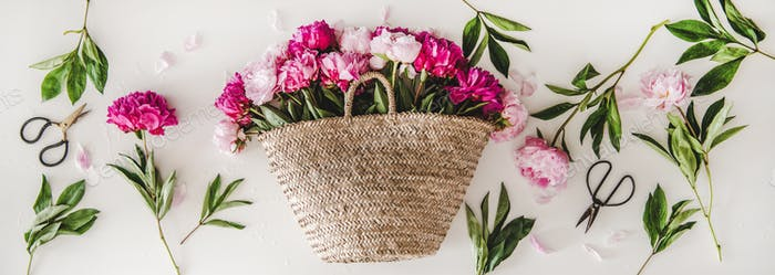 Summer flowers layout with pink and purple peonies in basket
