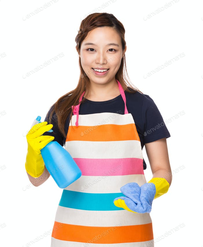 Housewife holding rag and detergent spray