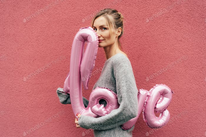 young elegant woman holds the inflated word LOVE on a pink background.