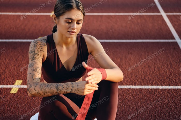 Beautiful sporty girl with tattoo in sportswear dreamily wrapping red boxing bandage on stadium