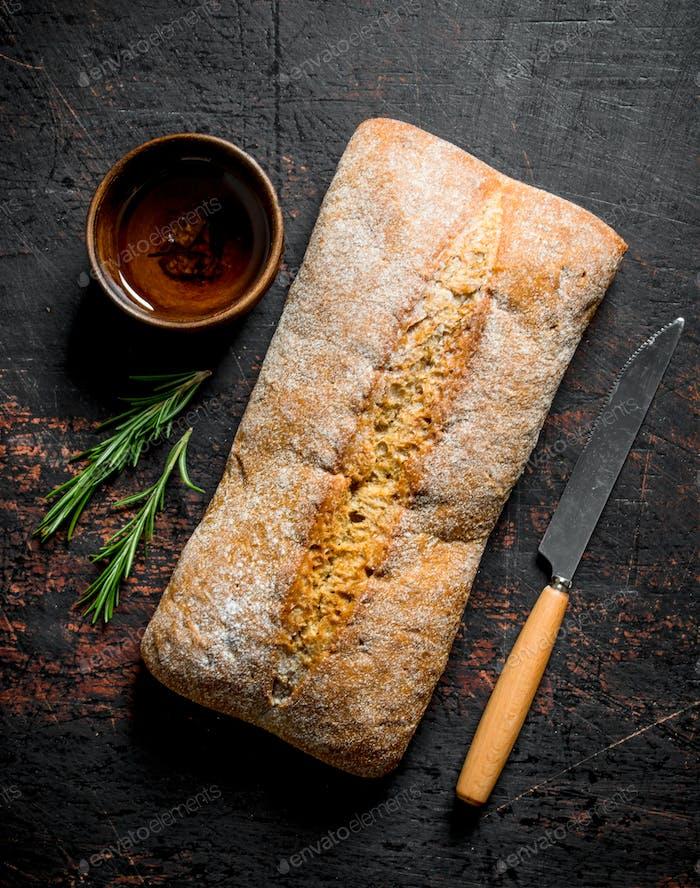 Ciabatta bread with knife and rosemary.