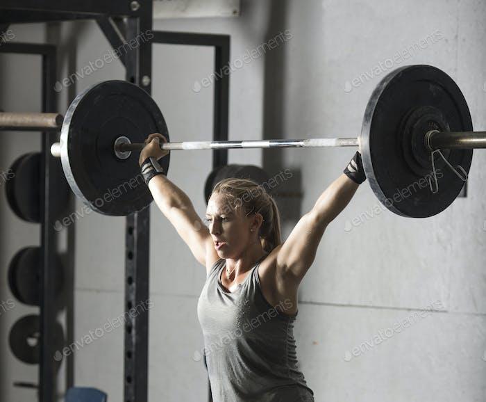 Nahaufnahme der starken jungen Frau, die Langhantel über den Kopf im Fitnessstudio heben.