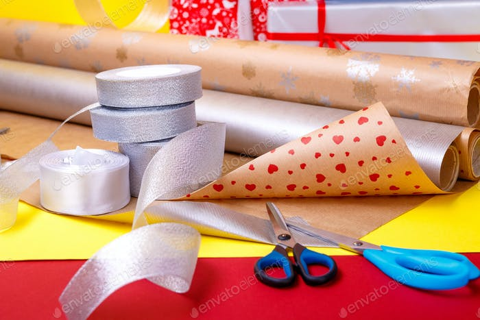 Gift wrapping, boxes, paper, ribbon and scissors on color background. Materials
