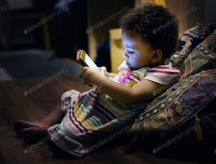 Brazilian toddler girl using mobile phone