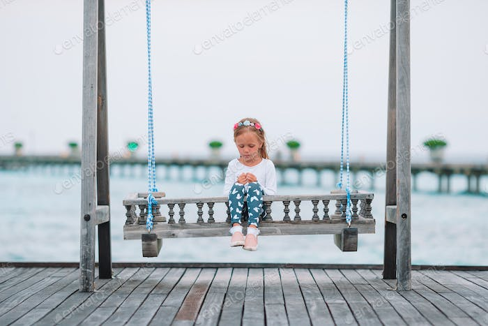 adorable little girl on swing at sunset