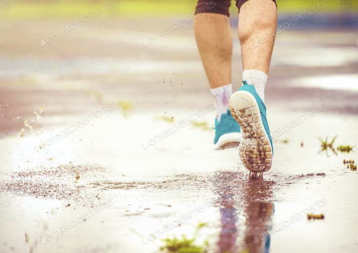 Junger Mann läuft bei Regenwetter
