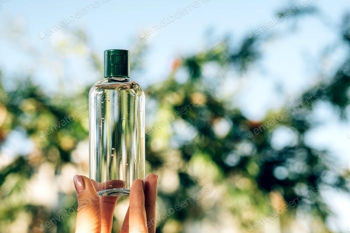 Frau Hand hält eine Flasche Alkohol Gel Desinfektionsmittel Flüssigkeit für die Reinigung der Hände