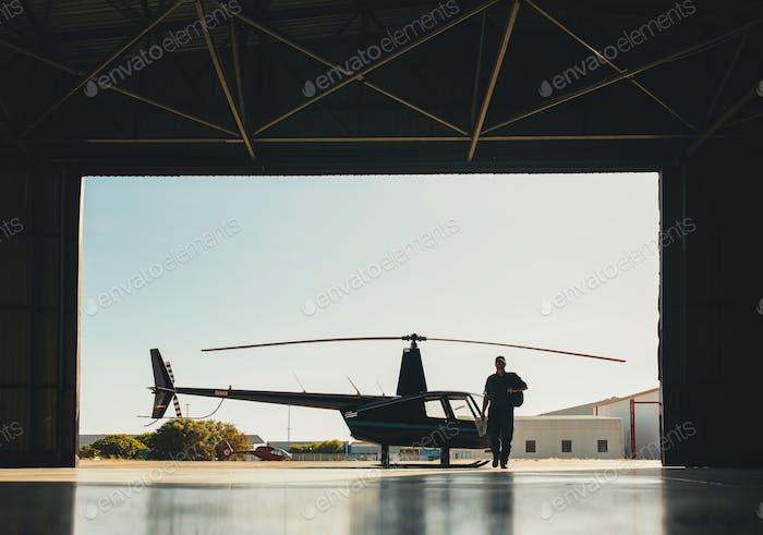 Piloto que llega al aeropuerto con un helicóptero en hangar