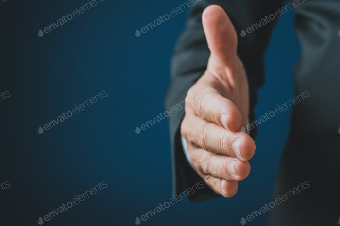 Hand of a businessman reaching in handshake