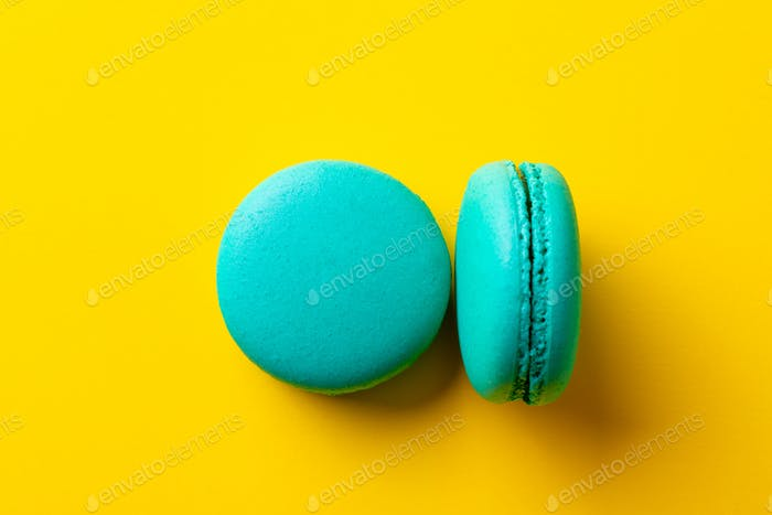 Macaroons dessert on yellow background. Close up. Top view.