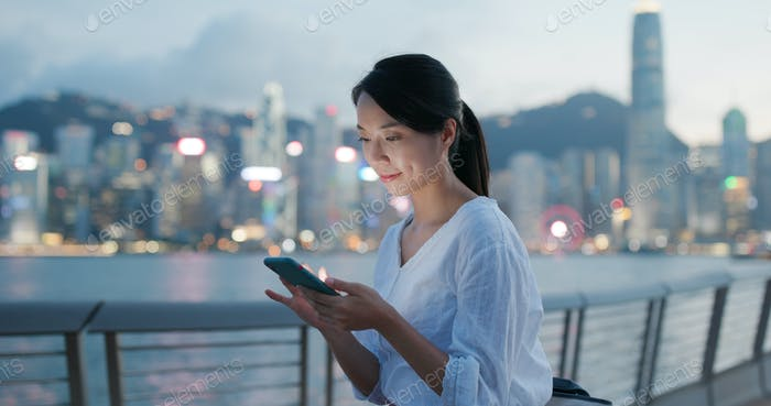 Woman sends sms on cellphone at night
