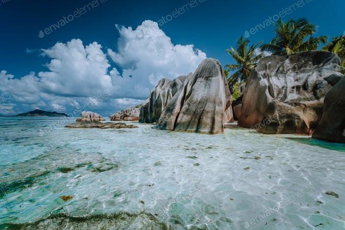 Granite boulders in shallow ocean water and white cloudscape on amazing Anse Source D'Argent