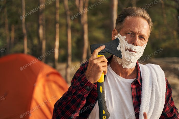 Mature man shaving with axe while going camping