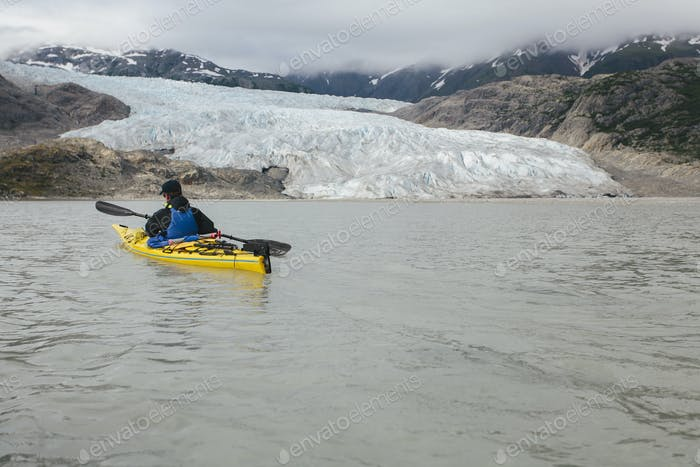 A sea kayaker approaches a glacier terminus, where the ice meets the sea.