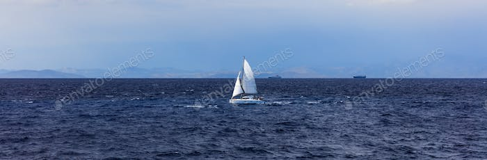 Sailing boat on a blue sky and sea background