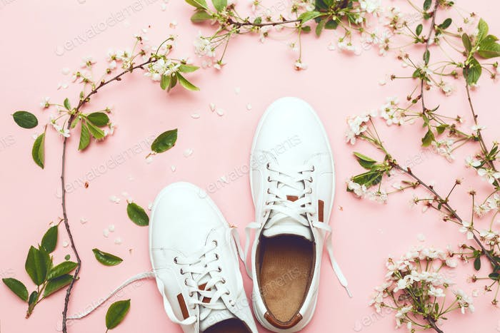White sneakers on pink background with spring bloom top view shot.