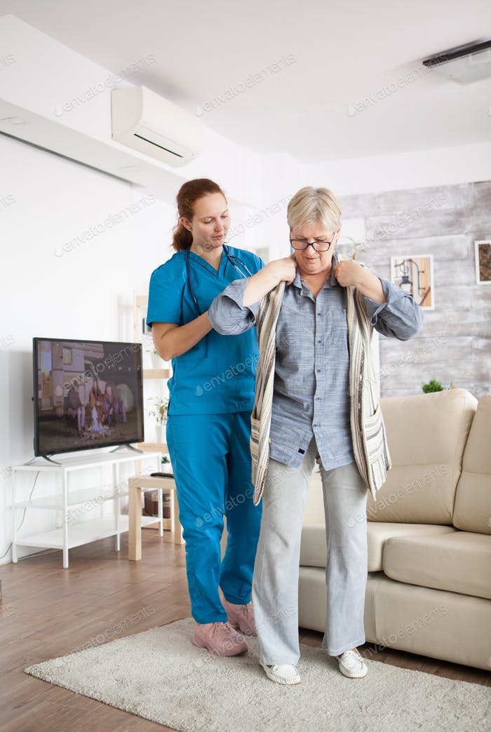 Young female nurse helping senior woman to get dressed