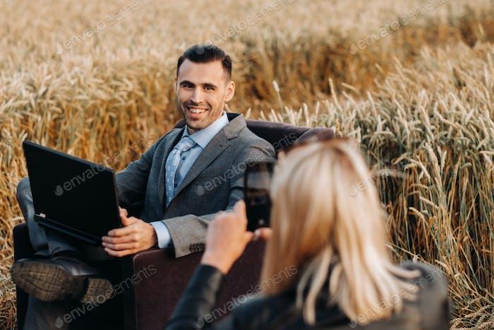 Портрет бизнесмена в костюме с ноутбуком, сидящего в кресле на пшеничном поле и