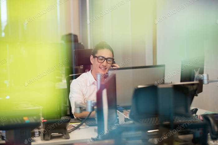 Smiling business executive talking on phone at office