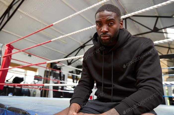 porträt von männlichen boxer tragen kapuze sweatshirt in gym sitzend auf boxing ring