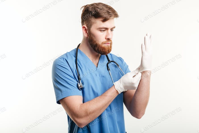 Portrait of a concentrated young doctor putting on sterile gloves