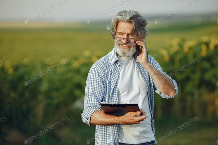 Old farmer in shirt standing on field with notebook