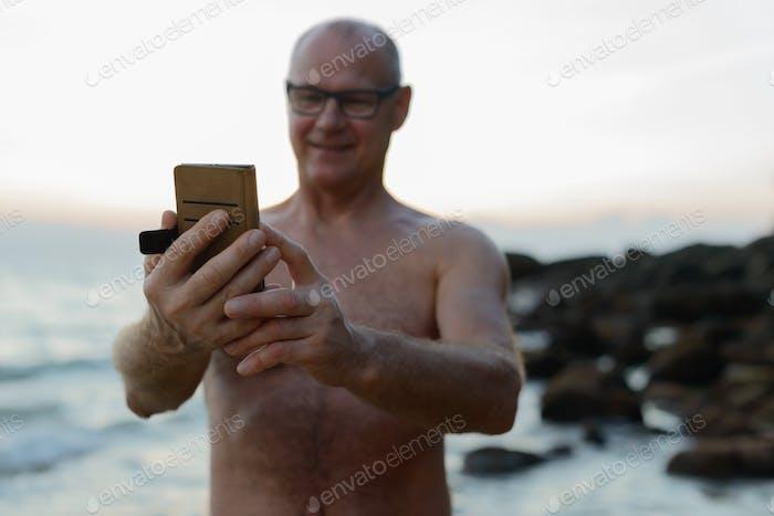 Mature handsome tourist man shirtless at the beach