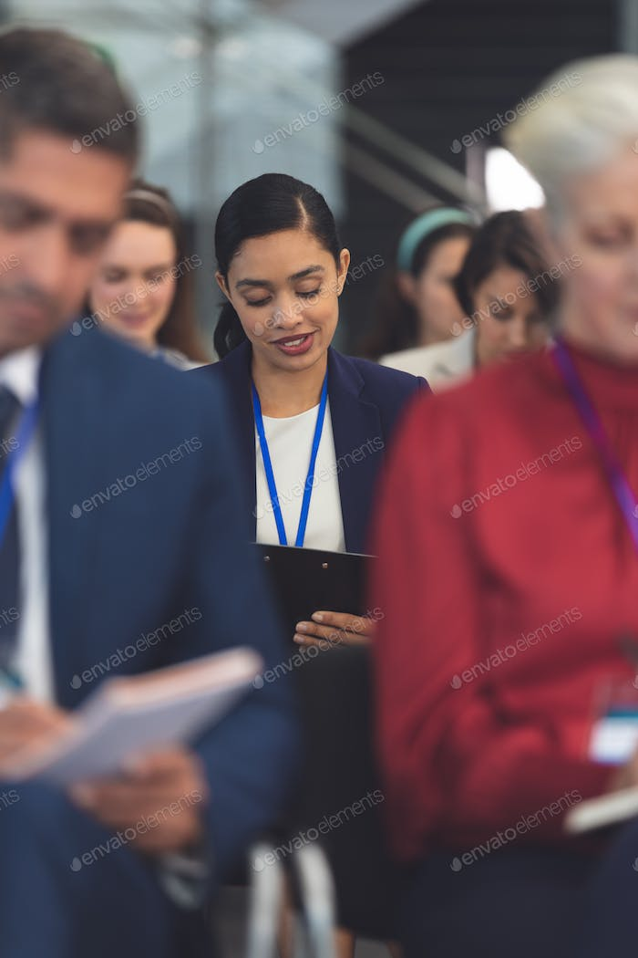 Businesswoman writing on notepad in a business seminar in office building