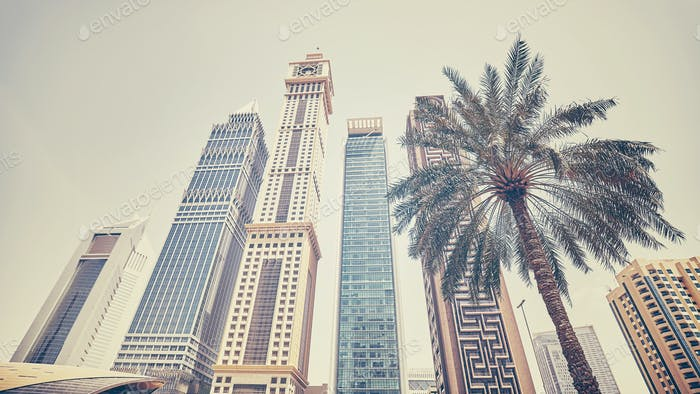 Retro stylized panoramic photo of Dubai skyscrapers with a palm