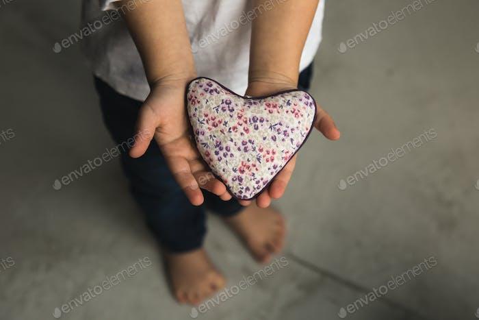 Baby Boy Hände geben Spielzeug Herz