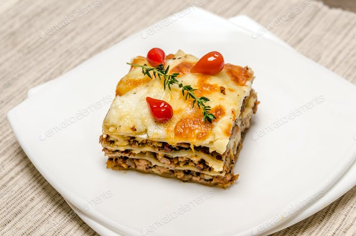 Portion of lasagna on the wooden table