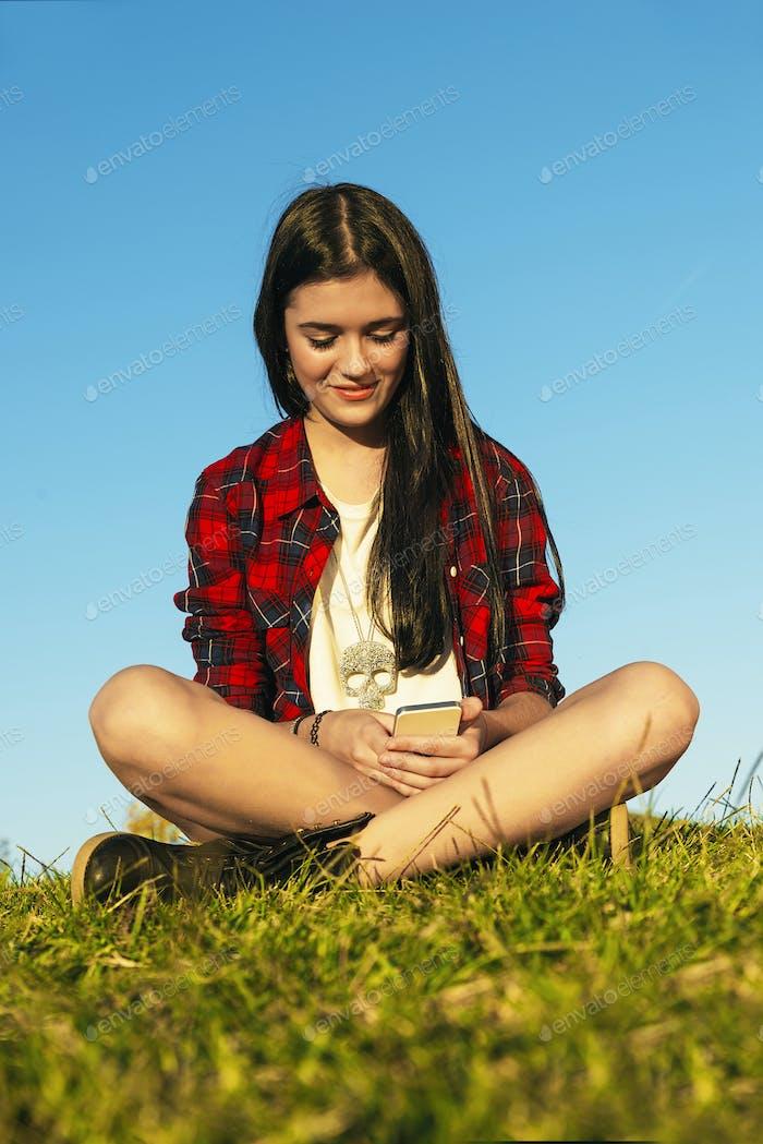 Happy Teenage Girl Using Mobile In Park