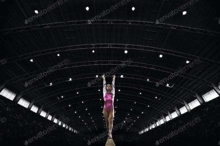 Eine junge Frau Turnerin, die auf dem Balken auftritt und auf einem schmalen Stück Apparat balanciert.