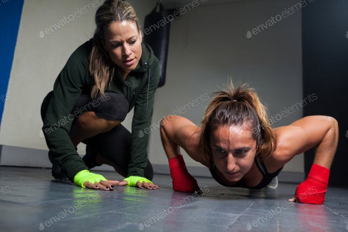 Trainer assisting woman in exercise