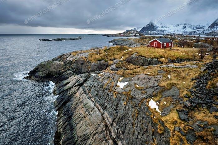 Klippe mit traditionellem rotem Rorbuhaus auf den Lofoten Inseln, Norwegen