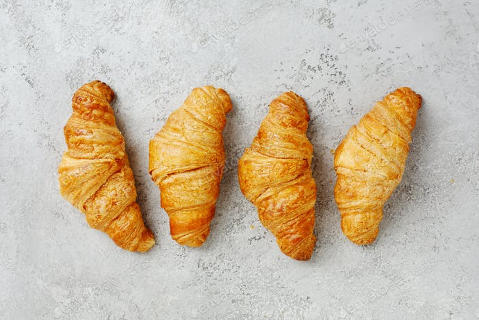 Croissants on a textured gray background.